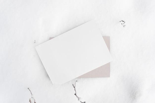 겨울 분위기 레이아웃. 종이, 눈, 마른 잔디의 빈 시트. 상위 뷰, 복사 공간. 텍스트를위한 빈 공간