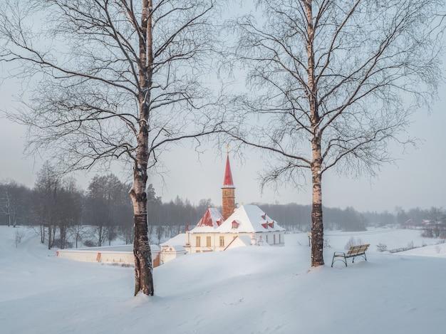 冬の朝の冷ややかな夜明け。美しい自然の風景の中に古いマルタの宮殿と白い雪の風景。ガッチナ。ロシア。