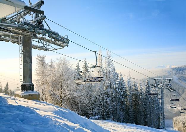 Зимний утренний горный пейзаж с подъемником и горнолыжным спуском