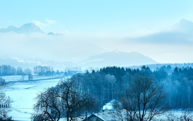 Winter morning mountain village hazy landscape with lowhanging clouds and castle in far austria.