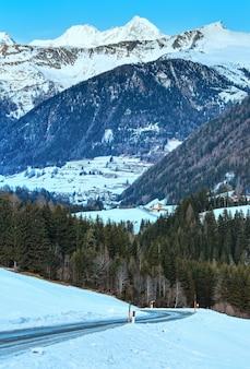 斜面に道路がある冬の山の田舎の風景(オーストリア)。