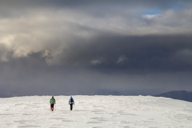 겨울 산 풍경입니다. 추운 겨울날 흐린 짙은 푸른 폭풍우가 치는 하늘 복사 공간 배경에서 먼 산을 향해 걸어가는 설원에 배낭을 메고 여행하는 관광객들의 뒷모습.