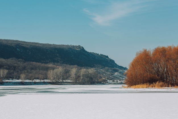 Winter mountain landscape, frozen river covered with ice and snow in sunny winter day