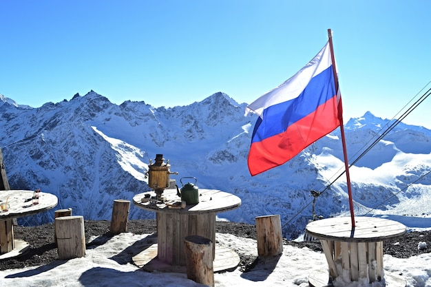 Winter mountain landscape, russian flag, samovar and cafes in the mountains Premium Photo