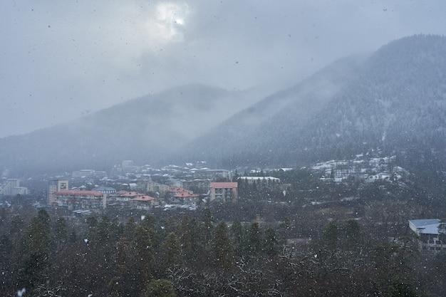 겨울 산 풍경입니다. 산 사이의 작은 마을. 구름이 도시 위에 매달려 있습니다.