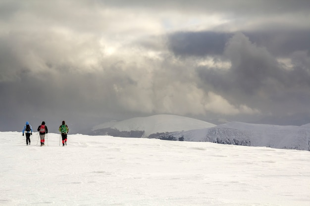 겨울 산 풍경. 흐린 진한 파란색 폭풍우 치는 하늘 복사 공간 배경에 먼 산을 향해 걷는 설에 배낭과 밝은 의류에 세 여행자 관광 등산객.