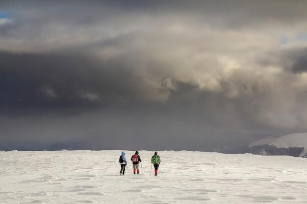 겨울 산 풍경. 흐린 진한 파란색 폭풍우 치는 하늘 복사 공간에 먼 산을 향해 걷는 설에 배낭과 밝은 의류에 세 여행자 관광 등산객.