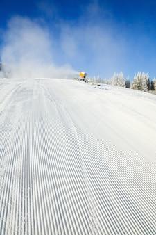 Зимний горный пейзаж со снегоуборочной машиной (снежной пушкой) на горнолыжном курорте буковель (украина)