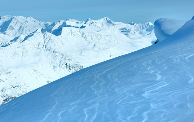 丘からの冬の山の風景と、前の斜面に輝く雪 (チロル、オーストリア)。