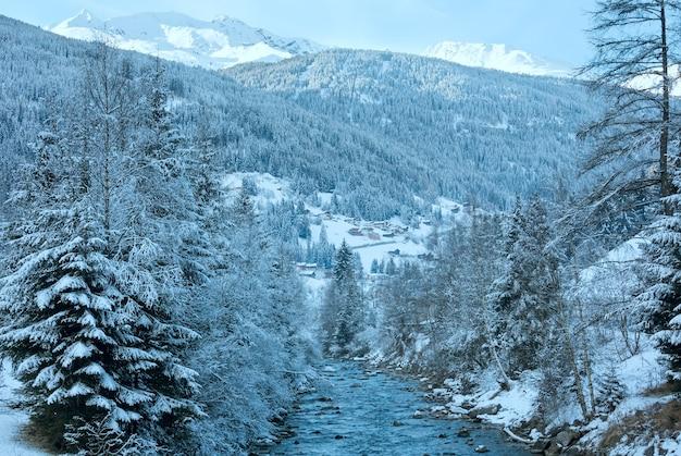 겨울 산 스트림보기 및 눈 덮인 숲과 언덕 (오스트리아)에 마을.