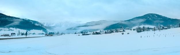 雲が低く垂れ下がる冬の山間の村のぼんやりとした風景(オーストリア)。