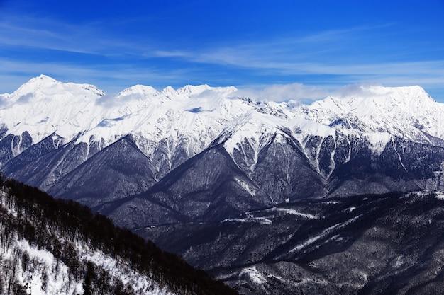 Зимние горы и голубое небо, вершины кавказского хребта.