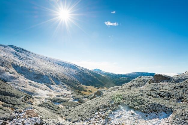 冬の山々とその下の日当たりの良い緑の谷。風景の丘と明るい太陽