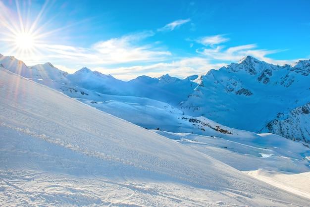 雪に覆われた日没の冬の山々
