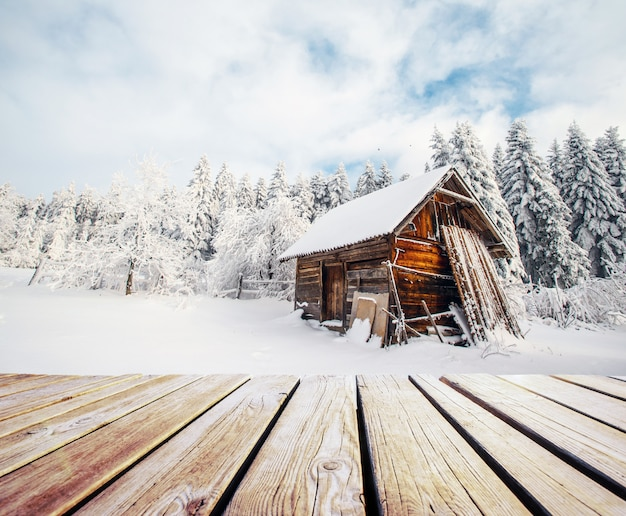 Winter mountains landscape with a snowy forest and a wooden hut and shabby table.