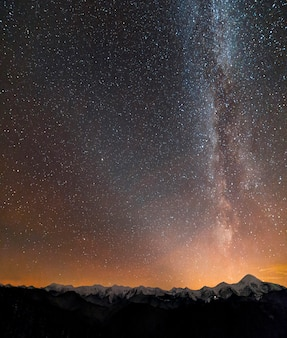 Winter mountains night landscape panorama. milky way bright cons