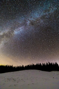 Winter mountains night landscape panorama. milky way bright constellation in dark blue starry sky over dark spruce pine trees forest, soft glow on horizon after sunset. wide angle shot.