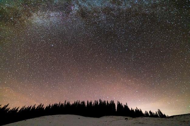 Зимние горы ночной пейзаж панорама. млечный путь яркое созвездие в синем звездном небе над темным еловым лесом сосен, мягкое свечение на горизонте после захода солнца.