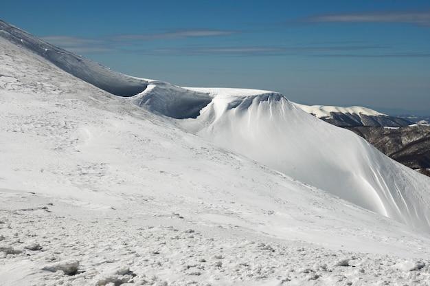 青いskに張り出したスノーキャップとスノーボードトラックがある冬の山の尾根