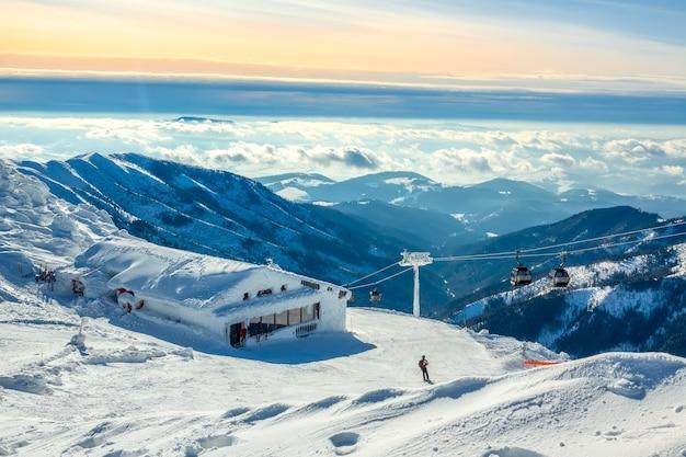 冬の山。雪をかぶった山頂と谷間の霧。ゲレンデの青とピンクの空。スキーリフトとバー