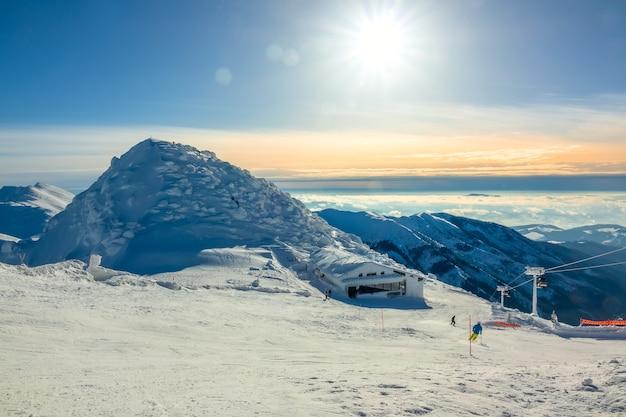 겨울 산. 계곡의 눈 덮힌 봉우리와 안개. 스키 실행을 통해 푸른 하늘에 밝은 태양. 스키 리프트 및 바