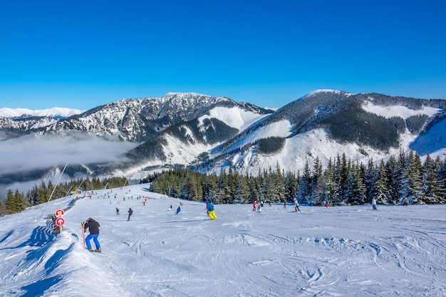 Winter mountains. wide and gentle ski slope in sunny weather. lots of skiers. light fog in the valley