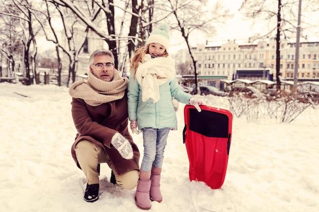 겨울 자연. 카메라에 포즈를 취하는 동안 그녀의 얼굴에 미소를 유지하는 매력적인 금발 소녀