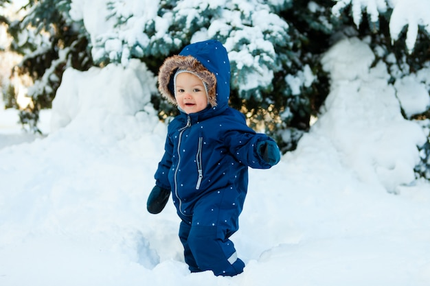 Winter, new year and christmas holidays, the child walks on snow in a warm winter overall,