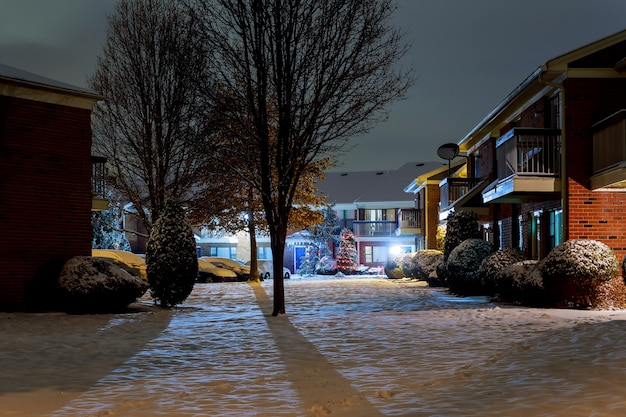 Winter night landscape - bench under winter trees and shining street lights with falling snowflakes