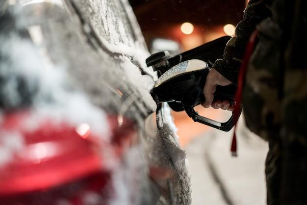 冬の夜に車に燃料を補給する