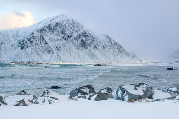 冬のノルウェー。雪をかぶった山々に囲まれた湾。