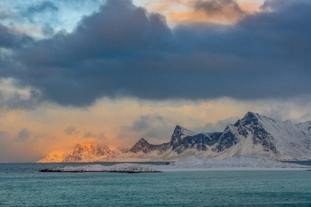 Winter norway. deserted mountainous coast of the ocean. thick clouds and sunlight