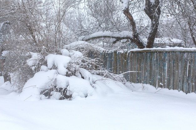 Winter old dilapidated rickety fence of wooden boards. a snow blizzard
