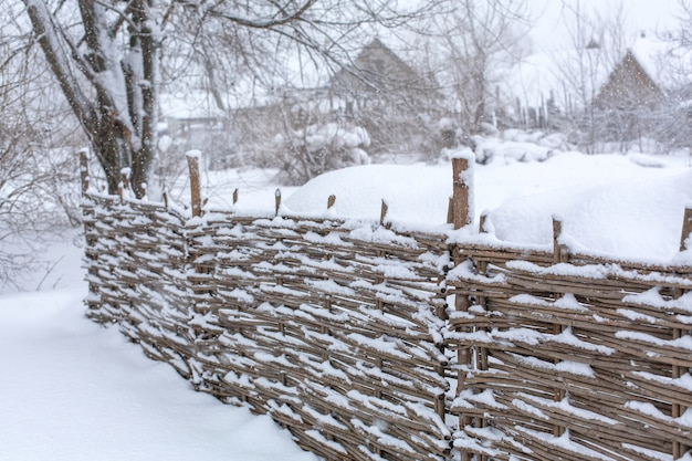 Winter old shabby wobbly wicker fence made of wooden boards. snow blizzard