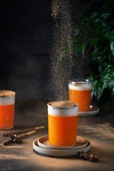 Winter ornage drink with milk, cinnamon and pumking on tha dark beckground