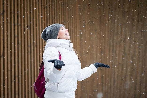 冬の屋外の肖像画。目を閉じて最初の雪を楽しんでいる白いジャケットに身を包んだ幸せなかわいい笑顔の白人の女の子。