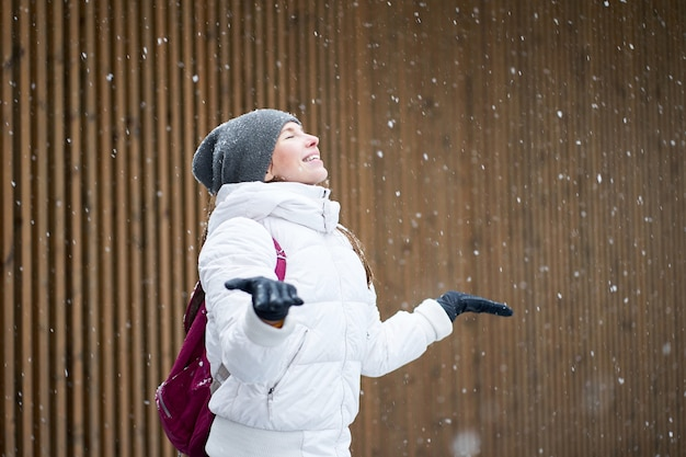 Winter outdoor portrait. happy cute smiling caucasian girl dressed in white jacket enjoying first snow with closed eyes.