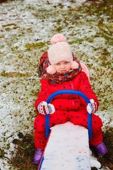 ニット帽とスカーフで愛らしい夢のような女の赤ちゃんの冬の屋外の肖像画。最初の雪を楽しんで屋外でかわいい遊び心のある女の子