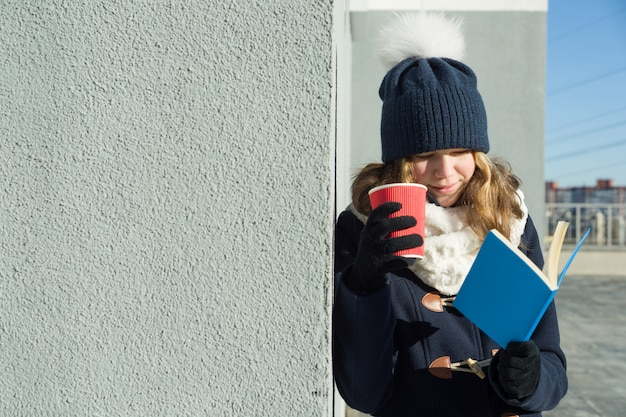 Winter outdoor portrait of young female student with book
