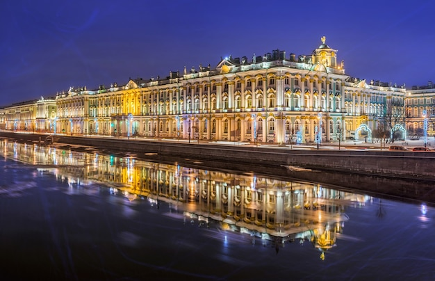 Winter palace in st. petersburg and its reflection in the neva on a winter night