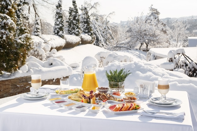 Winter pancakes breakfast on the terrace outside the restaurant on the background of snow pancakes, fruit, juice, and coffee