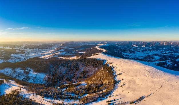 晴れた、風のない凍るような日にヨーロッパのスキーリゾートで雪の斜面の冬のパノラマ