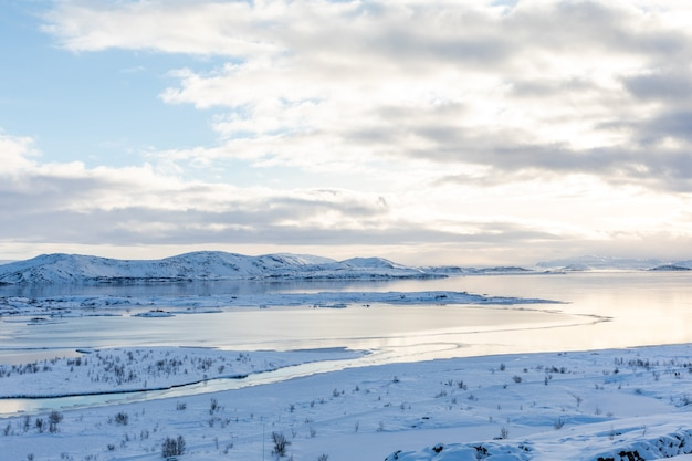 Зимняя панорама со снегом и льдом на озере тингвеллир, исландия, вид с парковки