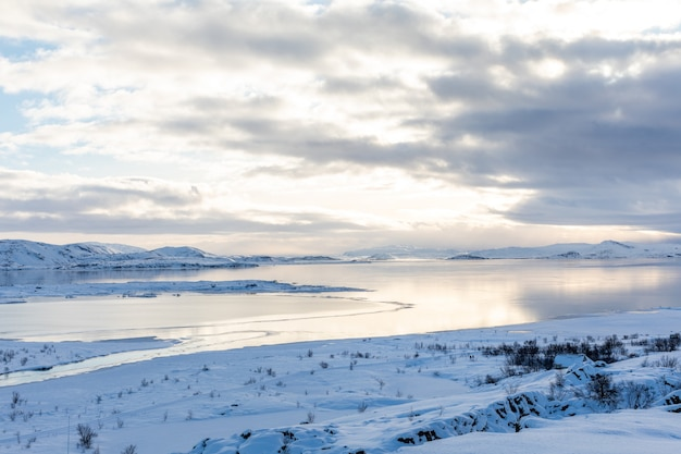 Winter panorama with snow and ice on lake thingvellir iceland view