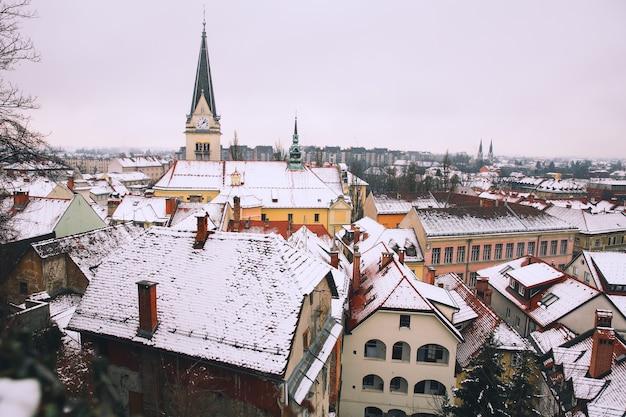 雪に覆われた赤い屋根の城からリュブリャナの冬のパノラマビュースロベニアヨーロッパ