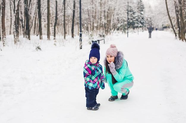 겨울, 부모와 자녀 개념-어머니와 딸이 걷고 눈 덮인 거리에서 재미