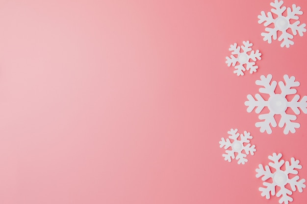 Winter pattern made of snowflakes and on pink . christmas . flat lay. copyspace for your text