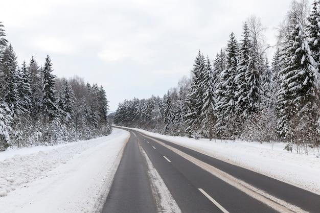 Зимняя асфальтированная дорога для автотранспорта, зимнее время года в снежную погоду