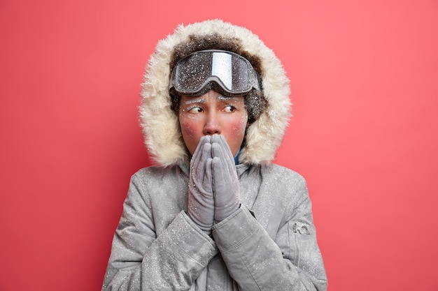 La foto invernale della donna etnica congelata riscalda le mani gelate soffiando aria calda si sente fredda durante una giornata gelida vestita con un cappotto caldo ha riposo attivo indossa occhiali da sci.