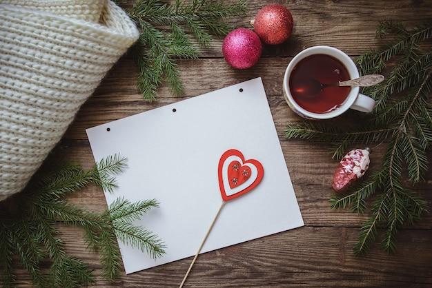 Зимний рисунок: чашка чая, еловые ветки, елочные игрушки, шарф и лист бумаги с сердечком на палочке на фактурной деревянной поверхности.